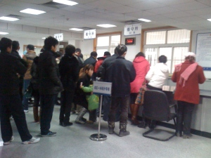 Family members line up to get inmate's room number before submitting cash to loved one inside.